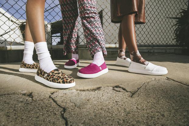 Three models' feet modeling Toms sneakers.