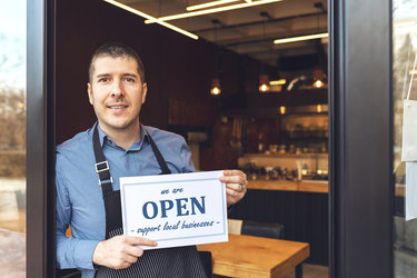 """A man wearing an apron stands in the entry way of his business. In the background, the store is outfitted with wood-top tables and shelves of dark bottles. The man holds a sign that says """"we are OPEN"""" and """"supporter small businesses."""" """"OPEN"""" is written in bold blue letters, with the other words arranged above and below in blue cursive."""