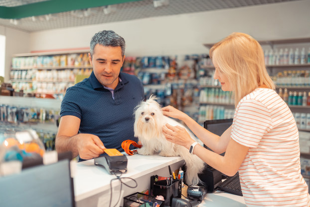 Grey-haired man paying for purchase with credit card in a shop.