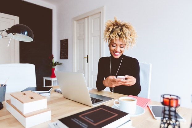 Woman smiling while sitting at her desk on her phone.