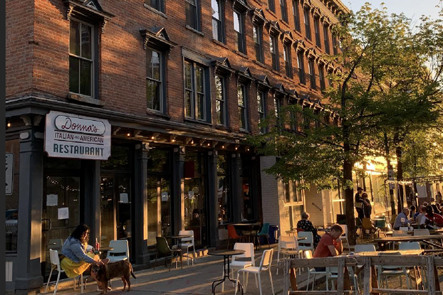 Outdoor seating outside a restaurant hosts customers with a tree and brick building in the background.