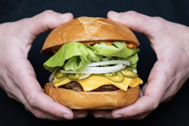 A tall cheeseburger with toppings is held in front of a black background.