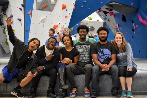 A jovial group of smiling people sit in a rock climbing room.
