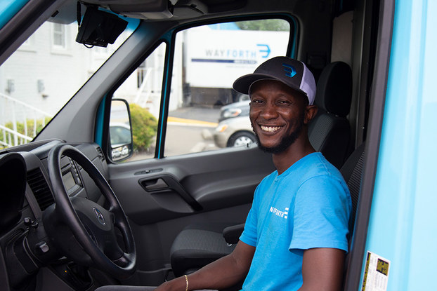 A smiling man wearing a cap sits in the driver's seat of a vehicle.