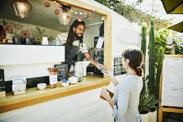 Man at mobile food truck register hands credit card back to customer.