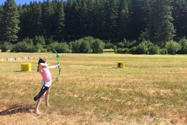 Woman taking archery lessons at Hyatt's Suncadia Resort.