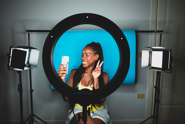 Influencer sitting in front of ring light and taking video on her phone.