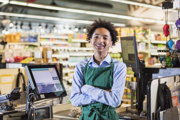 Adolescent boy at cash register in grocery store
