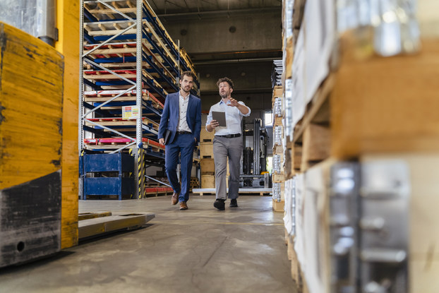 A wide shot of a pair of men walking through an aisle of a large warehouse. The man on the right is holding a clipboard and speaking to the man on the left, who wears a business suit. Behind them are large metal shelves holding wooden pallets. In the foreground, near the camera, are a forklift and a pile of pallets holding shrink-wrapped goods.