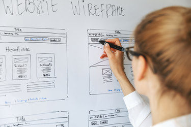 """A woman seen from behind adds to a drawing on a whiteboard. The drawings show various pages of a website and their layouts under the heading """"WEBSITE WIREFRAME."""""""