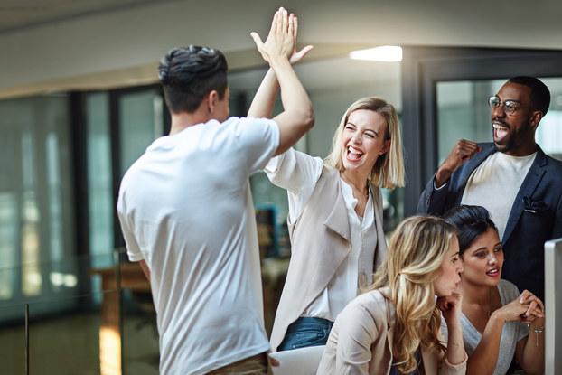 Several employees are in an office. Two of them are high-fiving and celebrating something. A third employee is also celebrating, standing near them and pumping his fist, his mouth open in a cheer. Two other employees are sitting at a computer in front of them, discussing something and not reacting to the people behind them.