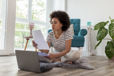 Woman looking over paperwork while working on laptop at home.