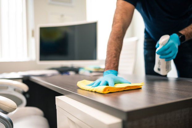 A person wearing light blue latex gloves uses a spray bottle and a yellow cloth to clean the top of a desk. The person's head and shoulders are out of frame. A room with large windows and a wide-screen TV can be seen out-of-focus in the background.