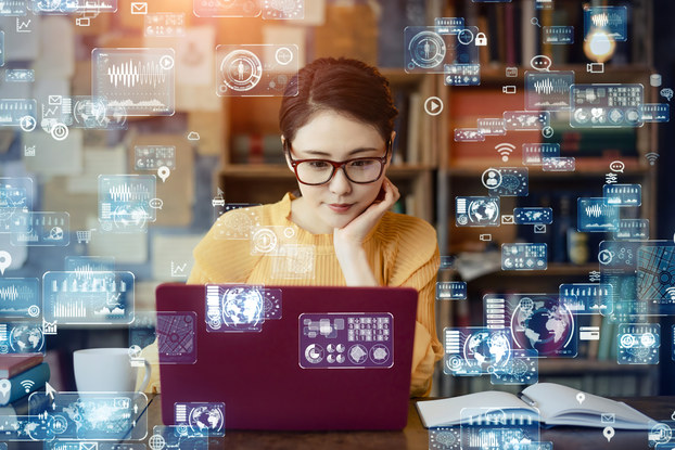Woman working on laptop with digital images representing artificial intelligence floating around her.