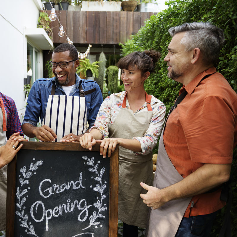 """A group of five people wearing aprons stand around a chalkboard sign. The sign reads """"Grand Opening"""" and the words are surrounded by a laurel wreath drawn in chalk. The five people are of different races and genders, and they stand with their hands on top of the sign, facing each other and smiling or laughing in celebration."""
