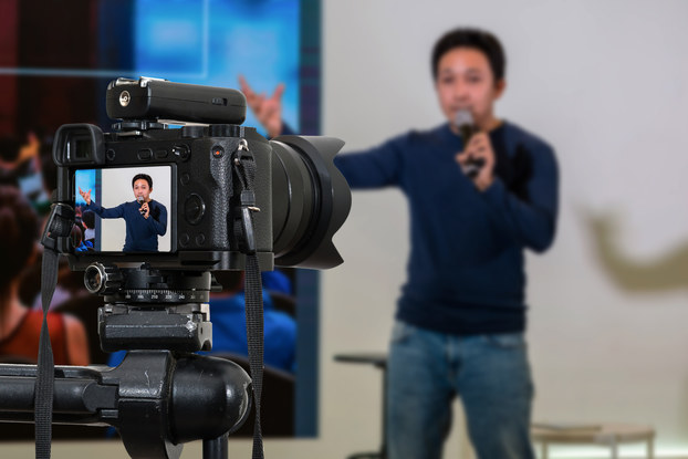 A camera, in focus, recoreds a man speaking on a microphone and gesticulating in front of a blank wall. The man can be seen on the camera's viewscreen and is shown out of focus in the background. To the left of the man is a screen showing the backs of members of an audience.