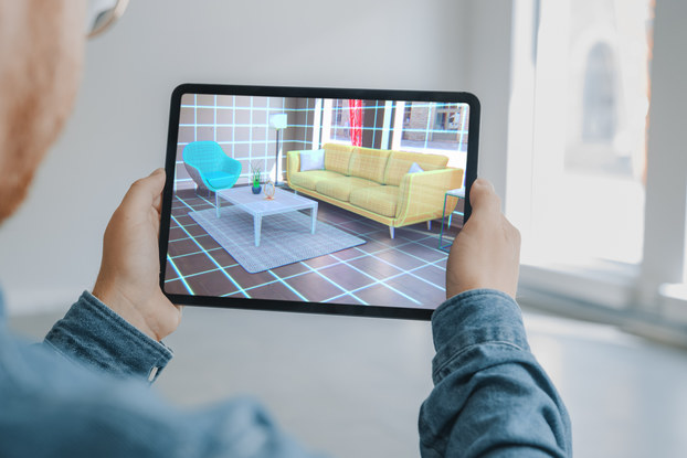 An over-the-shoulder shot of a man looking at a room through an electronic tablet. The room in the background is empty, but the room on the tablet screen is covered in a grid, with a couch, rug, coffee table, chair, lamp and wall art projected via augmented reality.