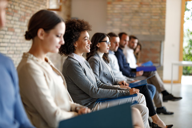 An angled side view of several job candidates dressed in business casual wear. The candidates are sitting in a row in a large room with brick walls. Most of the candidates are out of focus, but one woman in the middle is in-focus. She is looking up and straight-ahead at something out-of-frame, and she is smiling.