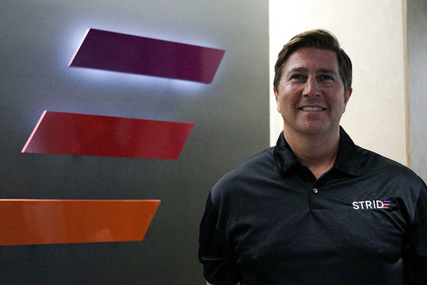 A shot of Jeff Stokes, president of STRIDE, standing next to the STRIDE logo (three parallel horizontal lines angled as if they're moving forward; the top line is purple, the middle red, and the bottom orange).