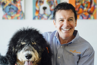 A headshot of Neil Gill, CEO of Dogtopia. He is sitting to the right of a large black-and-white dog wearing an orange bandanna and red collar.
