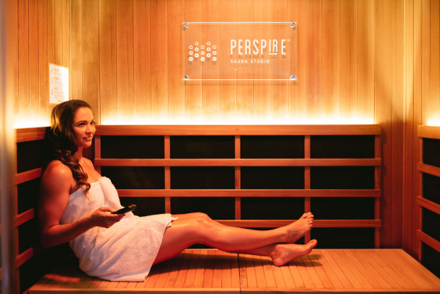 A woman wearing a towel and holding a remote control sits on a wooden bench in a Perspire sauna. The Perspire logo is on the wooden wall facing the camera.