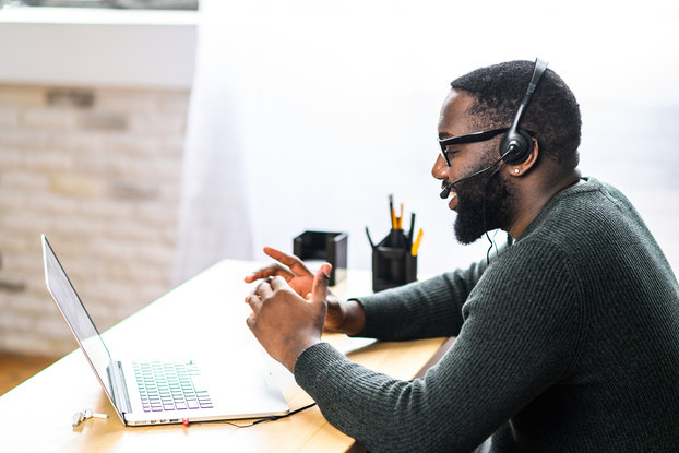 A man in profile sits at a desk facing an open laptop. He wears a headset and speaks into the attached microphone.
