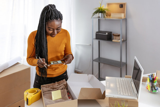 Young business owner packing cardboard box to deliver to a customer.