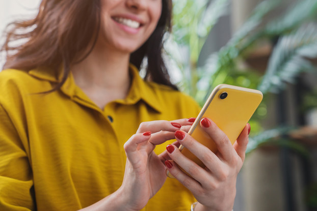 Woman smiling while looking at phone.