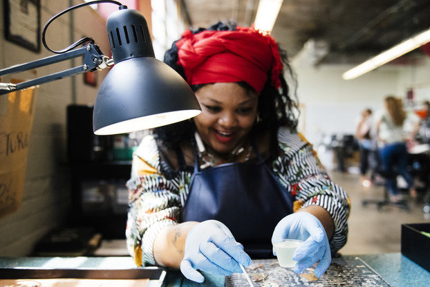 An employee of Rebel Nell works on a piece of jewelry made from fallen graffiti paint.