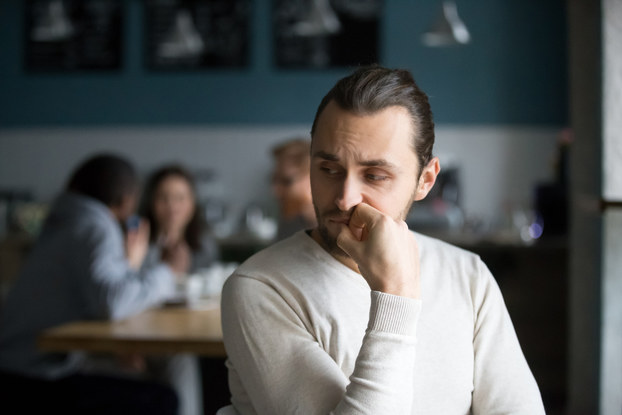 Upset male sits alone and appears upset.
