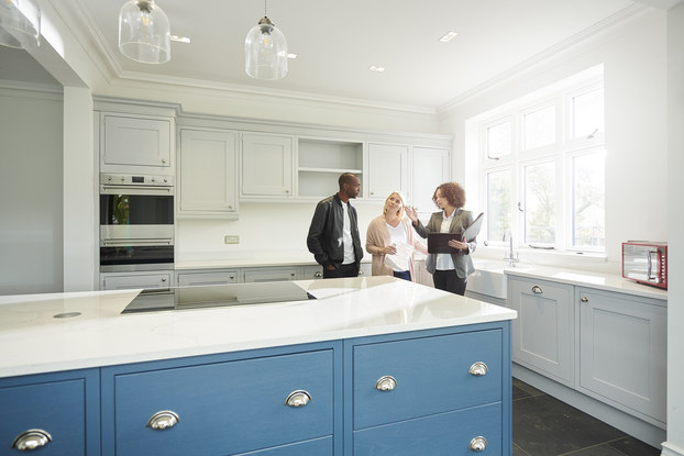 A real estate agent shows a couple around a home with new kitchen.