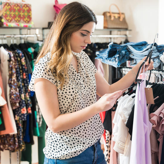 A young woman examines a price tag attached to a lavender tank top on a hanger. She's standing in a clothing store. Next to and behind her are clothing racks crammed with hanging shirts of various colors and styles. On top of the racks are folded jeans, sandals and purses.
