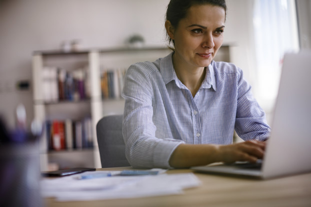 A young woman in a button-up shirt works on a laptop. Behind her, out of focus, is a book-lined set of shelves, and there are papers and pens on the desk beside her.
