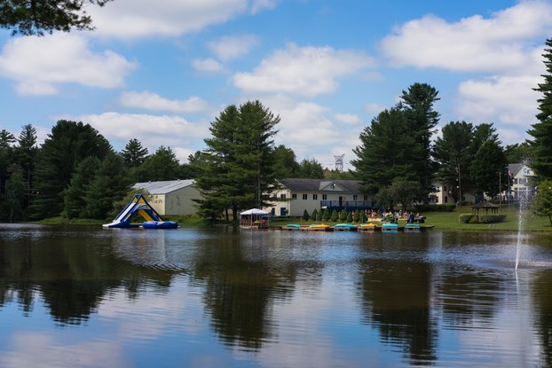 The lake at Camp Kennybrook in Monticello, New York. Across the lake can be see several buildings among pine trees, a blue-and-yellow inflatable water slide and several blue and yellow rowboats next to a wooden dock.