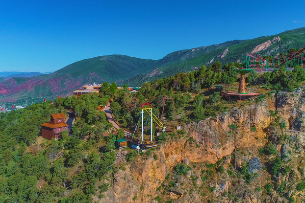 A longshot of Glenwood Caverns Adventure Park on top of a mountain in Glenwood Springs, Colorado. The park includes several wooden buildings, a roller coaster and two swinging structures.