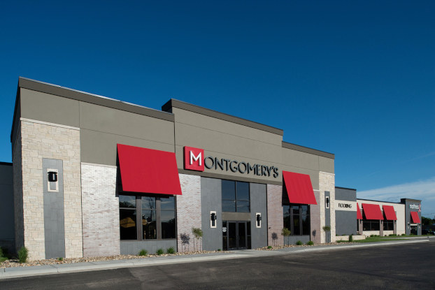 The exterior of Montgomery's furniture showroom in Watertown, South Dakota. The building is gray and white, with a smaller wing off to the right and red awnings over the windows.