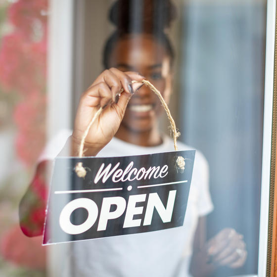 Woman holding welcome sign in front of business.