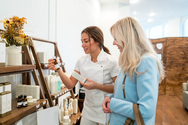 Customer consulting an employee in a beauty supply store.