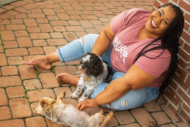 Courtney McWilliams, owner of MaryMac's Doggie Retreat, posing with dogs.
