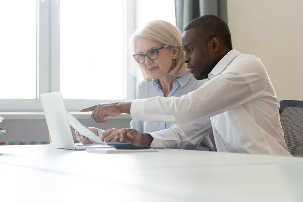 Employee pointing at laptop discussing information with colleague.