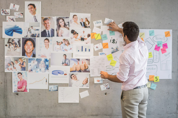 A man stands with his back to the camera in front of a gray concrete wall covers with photos of various people and objects and a large handwritten flowchart adorned with blue, orange, yellow and pink sticky notes.