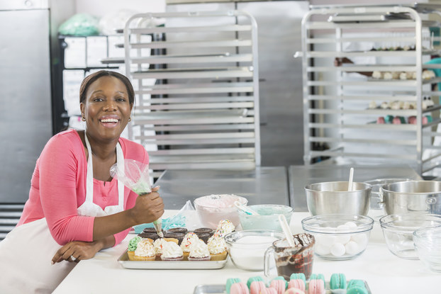 A Black woman wearing a pink shirt and a white apron leans against a counter in a large kitchen. On the counter beside her are mixing bowls, some filled with whipped icing, and trays of cupcakes iced with mint green, pastel pink, white and brown icing. An icing bag is in the woman's hand. In the background are cooling racks and industrial chrome refrigerators.