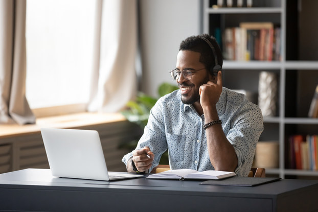 Person working on laptop at home wearing a headset and smiling.