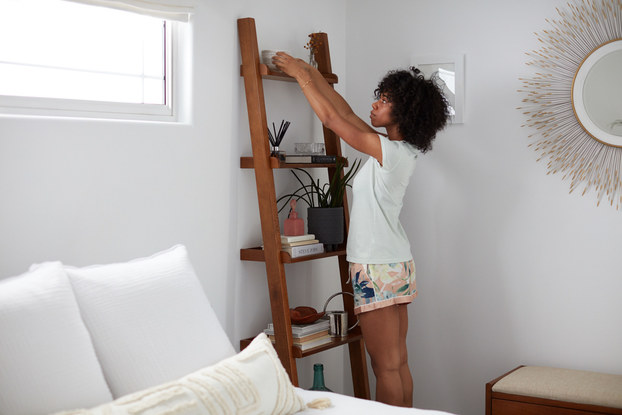 Woman decorating bedroom with furniture rentals from Fernish.