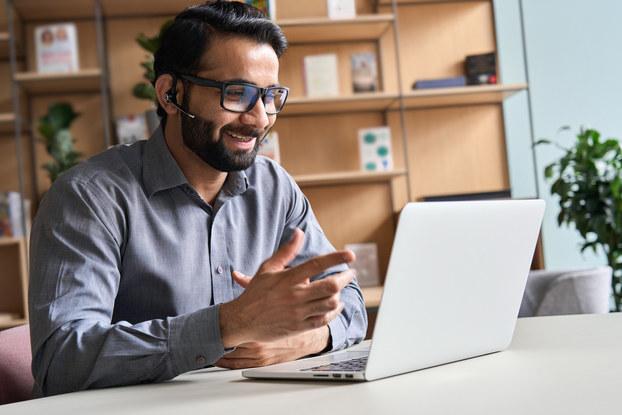 Business person wearing headset, talking at virtual meeting.