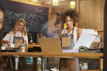 a coffee shop owner uses a computer to check bills. In the background two staff attend to the orders.