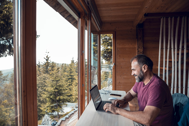 Close up of a mid-adult man working on a laptop from his cabin in the woods