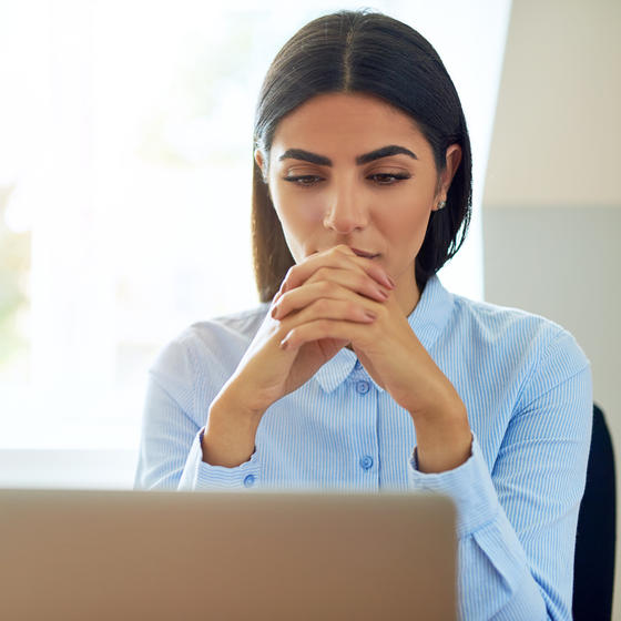Serious young businesswoman with a worried expression sitting reading information on her laptop with clasped hands.
