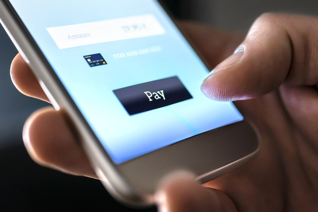 """A close-up on a hand holding a smartphone. The thumb hovers over a button reading """"Pay"""" on the phone's screen."""