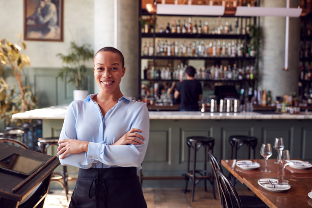 Portrait of confident female owner of restaurant bar standing by hostess stand